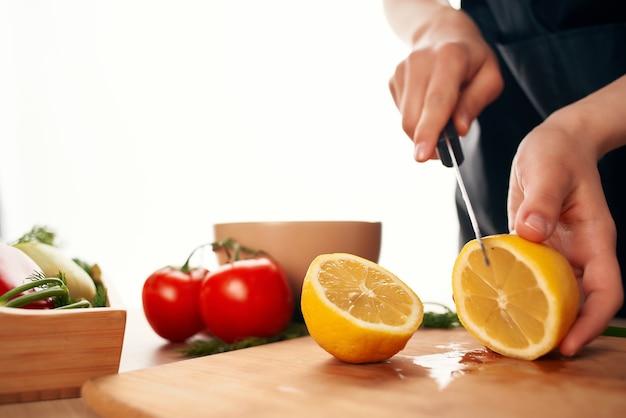 Krojenie cytryny na deskę nożem do gotowania składników kuchennych