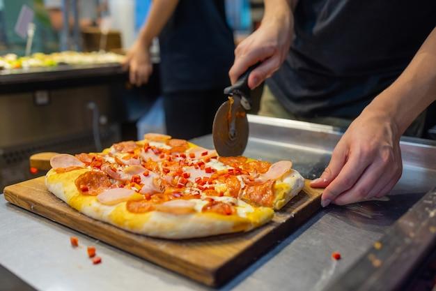 Krojenie gotowej pizzy męskimi rękami nożem