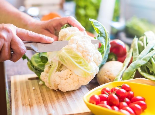 Krojenie kalafiora w kuchni ręce starszej pani kroją i myją wszelkiego rodzaju warzywa