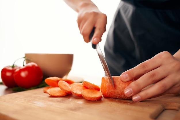 Krojenie marchewki na desce do krojenia z nożem do gotowania w kuchni. zdjęcie wysokiej jakości
