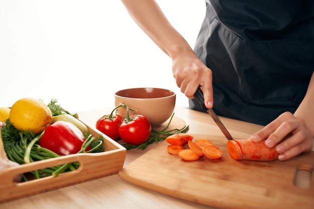 Krojenie marchewki na deskę do krojenia nożem gotowanie świeżych warzyw