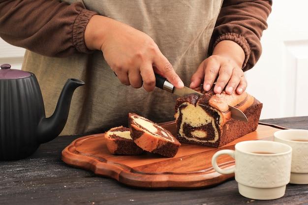 Krojenie marmurowego ciasta, żeński nóż piekarza do krojenia bochenka marmerowego ciasta w kuchni, przed podaniem z herbatą na popołudniową herbatę