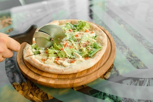 Krojenie pizzy nożem do pizzy z szynką, salami, pomidorami, sałatką i parmezanem na drewnianej desce na szklanym stole