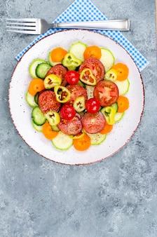 Krojenie warzyw sezonowych warzyw na talerzu na tle szaro-niebieskim. zdjęcie studyjne.