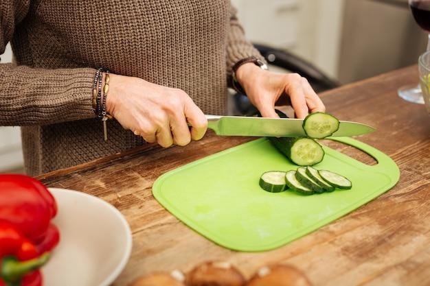 Krojenie warzyw. uważna pani w ciepłym swetrze kroi ogórek podczas gotowania lekkiego obiadu dla siebie