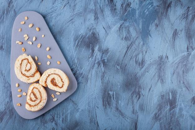 Krojona rolka biszkoptowa z nadzieniem czekoladowym umieszczona na szarej desce.