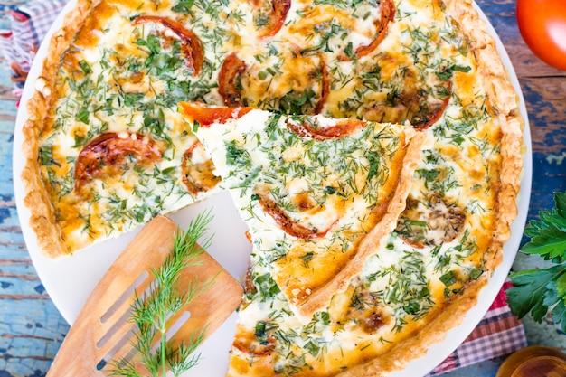 Krojone domowe francuskie ciasto quiche z pomidorem, serem i ziołami na talerzu. widok z góry
