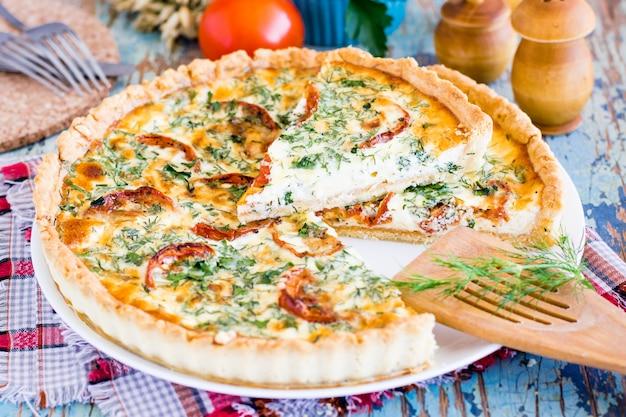 Krojone domowe francuskie ciasto quiche z pomidorem, serem i ziołami na talerzu.