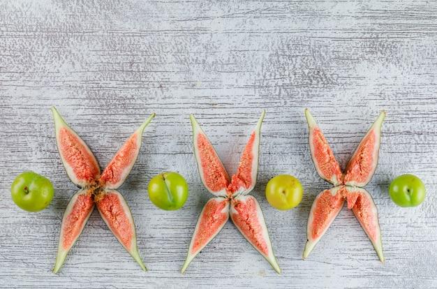 Krojone figi z zielonymi śliwkami na grungy,