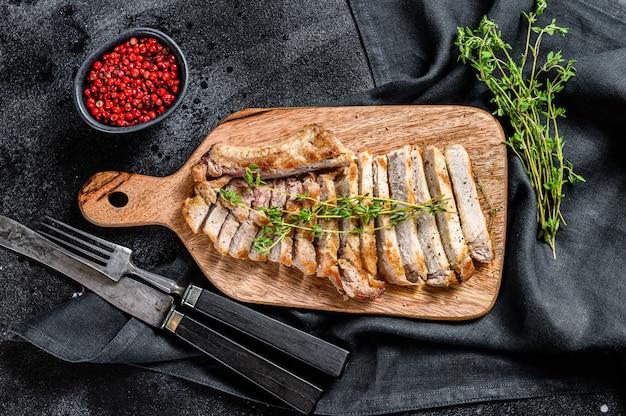 Krojone kotlety wieprzowe z grilla. organiczny stek z mięsa. czarne tło. widok z góry