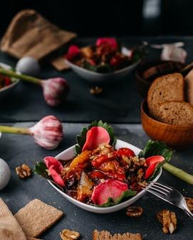 Krojone mięso wraz z pokrojonymi warzywami zielone liście wewnątrz białego talerza wraz z chrupiącymi bochenekami chleba na szaro