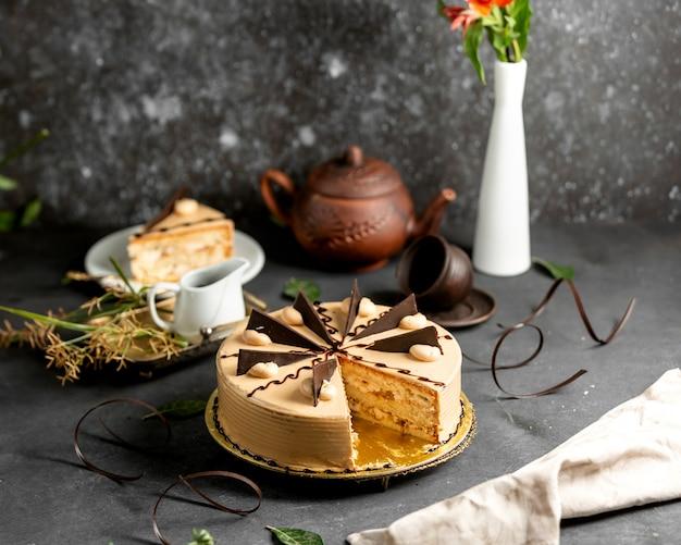 Krojone okrągłe ciasto z kawałkami śmietany i czekolady