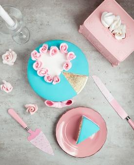 Krojone turkusowe ciasto z białym sercem i różowymi różami na górze
