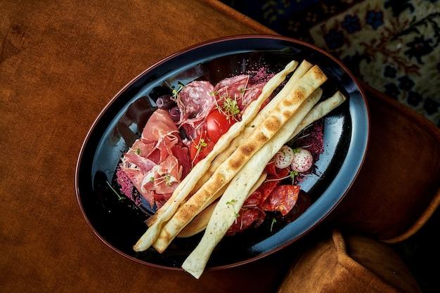 Krojone włoskie chorizos, salami, prosciutto di parma podawane na czarnym talerzu. jedzenie w restauracji. widok z góry na smaczne włoskie przystawki mięsne