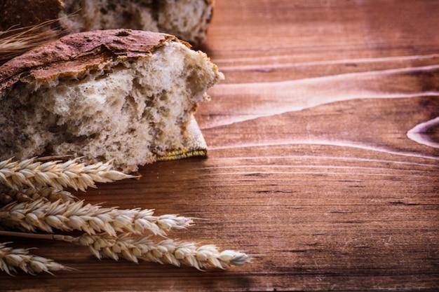 Krojonego chleba i kłosów żyta na vintage, drewniana deska wersja pozioma koncepcja żywności i napojów