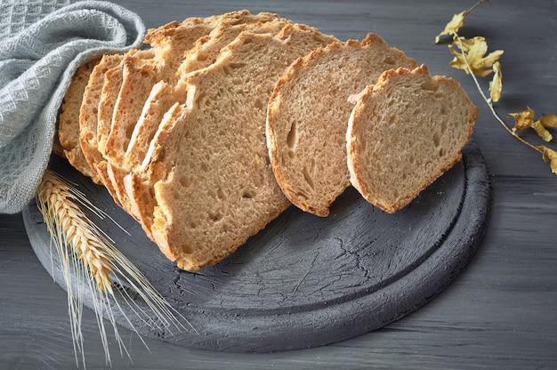 Krojony biały okrągły chleb z kłosami pszenicy na szarym rustykalnym drewnie