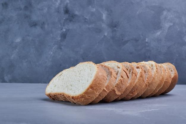 Krojony chleb na niebieskim stole.