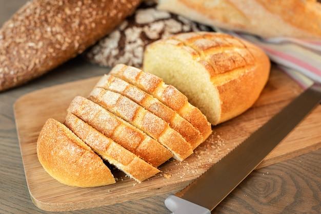 Krojony chleb na stole na tle różnych pieczywa.