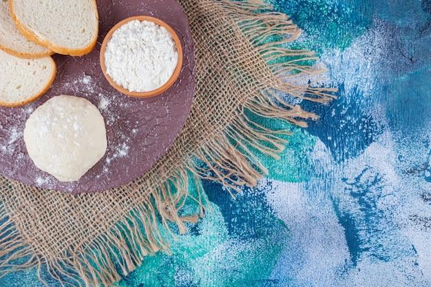 Krojony czarno-biały chleb na kawałku drewna z miską mąki i żółtkiem.
