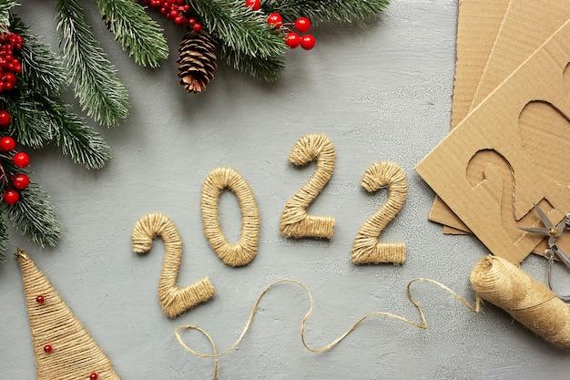 Krok 6. numery diy 2022 wykonane z tektury i liny lnianej. koncepcja przygotowań do świąt bożego narodzenia i nowego roku.
