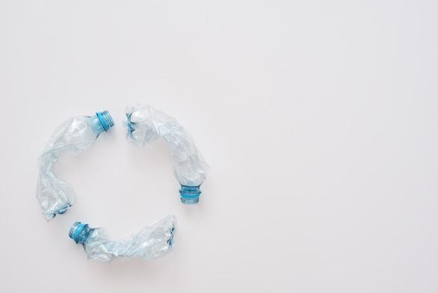Krok do zielonego życia. na białym tle koło zgniotu plastikowych butelek. gospodarka odpadami i recykling. koncepcja sortowania śmieci