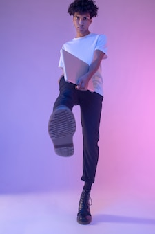 Krok naprzód. afroamerykanin młody facet w białej koszulce z laptopem co krok