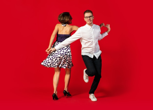 Krok. oldschoolowy styl młoda para taniec na białym tle na czerwonym tle studio. moda artystyczna, koncepcja ruchu i działania, kultura młodzieżowa, powrót mody. młody stylowy mężczyzna i kobieta.