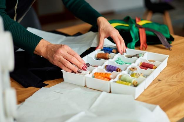 Krok po kroku, kobieca ręka krawcowa wyciąga nić z pudełka, dojrzały krawiec pracujący w atelier, przemyśle tekstylnym, hobby, miejscu pracy.