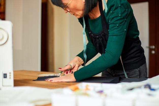 Krok po kroku, krawcowa kobieta na stole tnąca materiał nożyczkami, dojrzały krawiec pracujący w atelier, przemyśle tekstylnym, hobby, miejscu pracy.