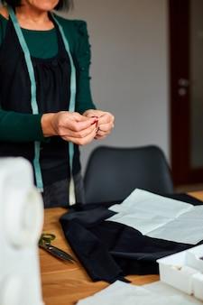 Krok po kroku, krawcowa kobieta wciągająca nitkę w igłę, dojrzała krawcowa pracująca przy szyciu w atelier, przemyśle tekstylnym, hobby, miejscu pracy.