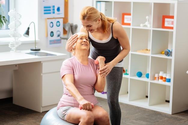 Krok po kroku. pozytywna, ciężko pracująca kobieta podnosząca małe hantle, jednocześnie stopniowo rozwijając swoje mięśnie