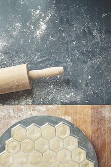 Krok po kroku proces robienia domowych pierogów, ravioli lub pelmeni z nadzieniem z mięsa mielonego na foremce do ravioli lub ravioli. widok z góry czerwone pierożki w formie na białym tle na niebieskim starym stole