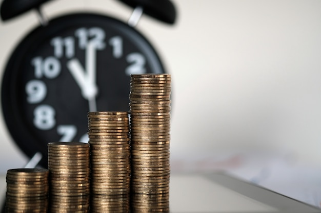Krok stosy monet i budzik z komputera typu tablet