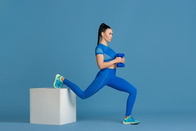 Kroki. piękna młoda lekkoatletka praktykujących, monochromatyczny niebieski portret. sportowy dopasowany model brunetka ze skokiem, ciężarkami. koncepcja odnowy biologicznej, zdrowego stylu życia, piękna i działania.