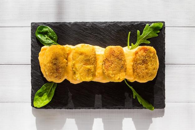 Krokiety z żółtym sosem, sałatką kukurydzianą i rukolą na czarnym kamiennym talerzu w słonecznej kuchni.