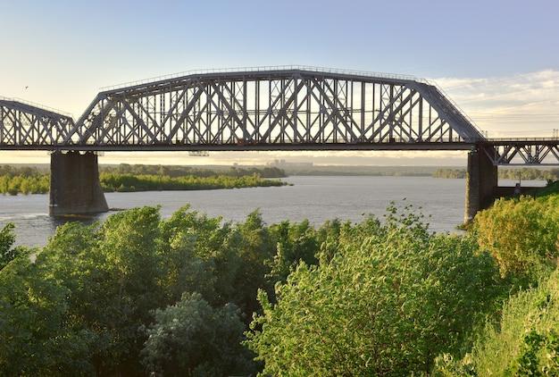 Krokwie metalowego mostu na wysokich podporach brzegu wielkiej syberyjskiej rzeki