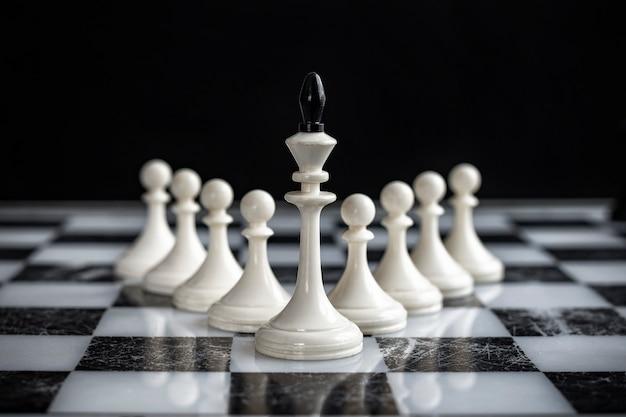 Król i pionki na szachownicy na ciemnym tle.