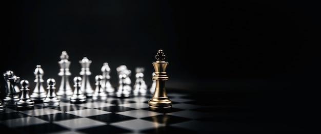 Król złote szachy stojące naprzeciw srebrnej drużyny szachowej