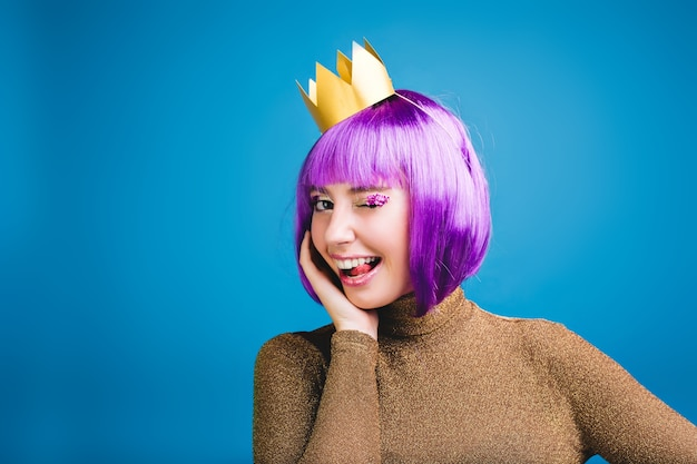 Królewski portret radosnej młodej kobiety w luksusowej sukience, złota korona zabawy. pokazanie języka, radości, figlarnego wesołego nastroju, wspaniałej imprezy, obciętych fioletowych włosów.