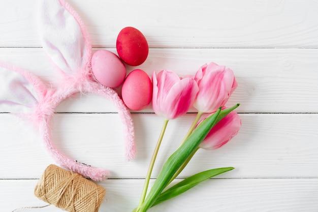 Królicze uszy z tulipanów i kolorowych jaj na drewniane tło płaskie nieatutowy