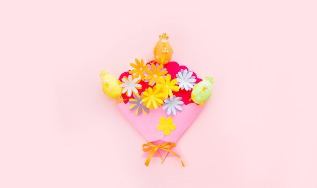 Króliczek i kwiaty rzemiosła na różowym tle w wielkanocny dzień. świętujemy wielkanoc na wiosnę. widok z góry.