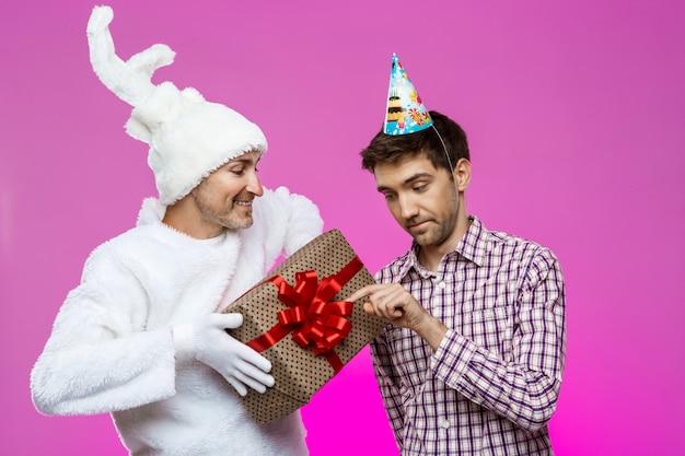 Królik daje prezent urodzinowy pijanemu mężczyźnie ponad fioletową ścianą.