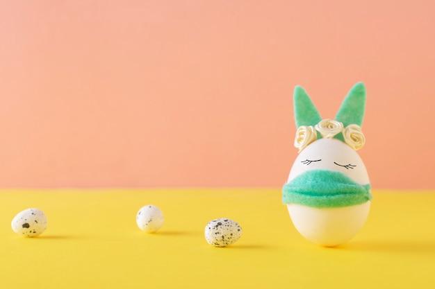 Królik-jajko w maskach ochronnych na żółtej ścianie z miejsca na kopię. koncepcja covid-19, zostań w domu.