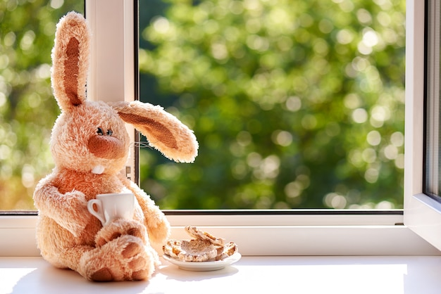Królik z filiżanką kawy i ciastkami rano w pobliżu otwartego okna. dzień dobry i szczęśliwy dzień. skopiuj miejsce.