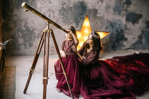 Królowa i jej córka księżniczka patrzące na gwiazdy przez teleskop na poddaszu