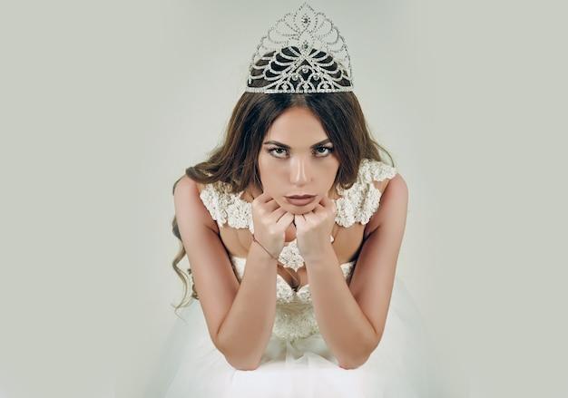 Królowa kobiety. salon piękności i moda ślubna. pielęgnacja włosów i królowa balu. kobieta z długimi włosami białą sukienkę i koronę.