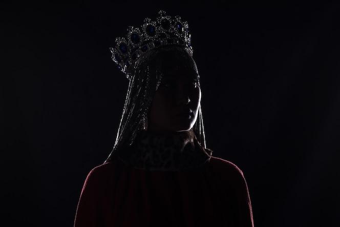 Królowa z koroną portret studyjny na czarnym tle