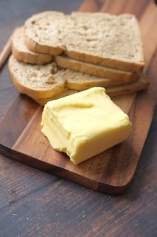 Kromka masła i pełnoziarnisty chleb na desce do krojenia