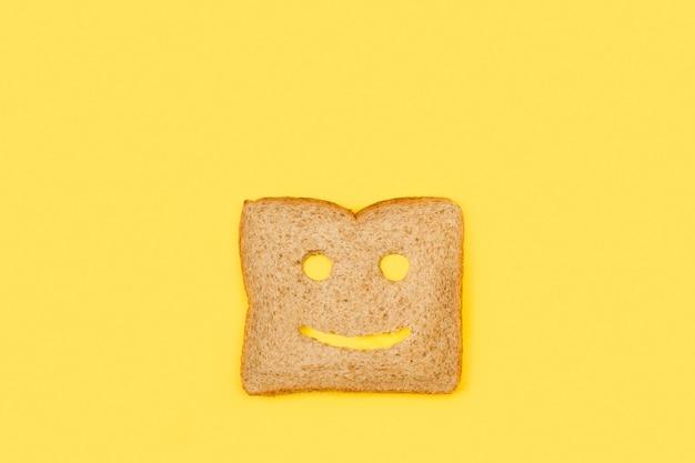 Kromka pełnoziarnistego chleba o kształcie twarzy