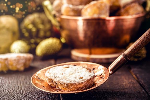 """Kromka smażonego chleba z cynamonem i cukrem w starym miedzianym cedzidle. deser zwany w brazylii """"rabanada"""", typowy brazylijski deser bożonarodzeniowy."""